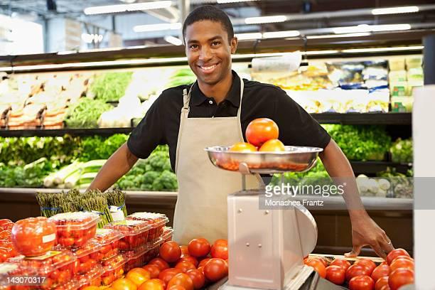 Worker weighing fruit in supermarket