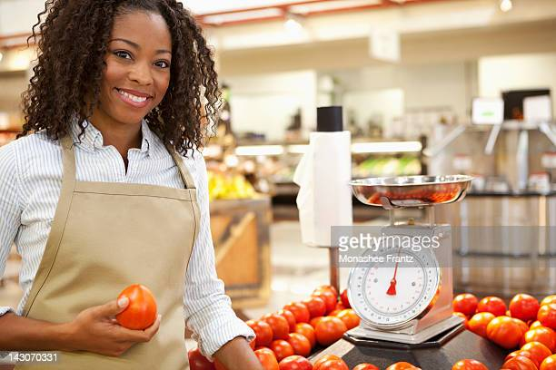 Worker weighing produce in supermarket