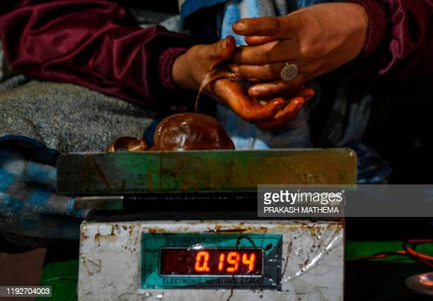 A worker weighs molten raw hardened molasses locally know as Chaku for the upcoming Maghe Sankranti festival in Tokha on the outskirts of Kathmandu...