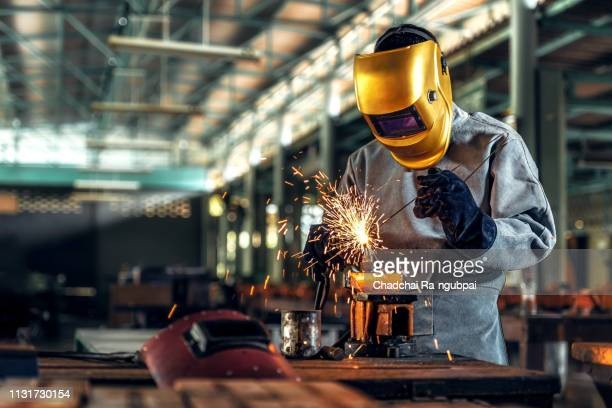 worker welder working welding steel in industry with safety mask safety gloves and safety equipment. worker welding concept. - male erection stock pictures, royalty-free photos & images