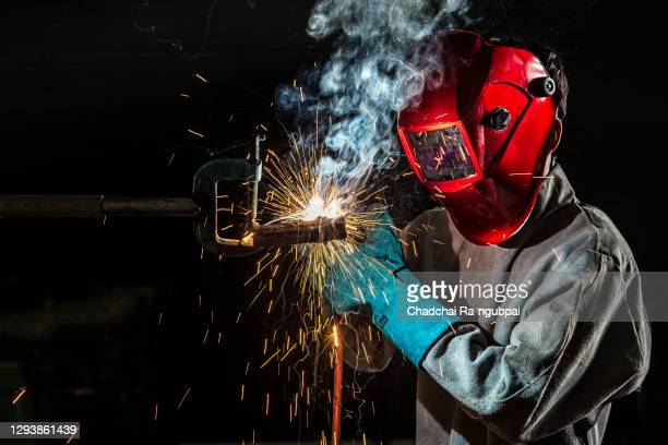 worker welder working welding steel in industry with safety mask safety gloves and safety equipment. wolker welding concept. - fabricage apparatuur stock pictures, royalty-free photos & images