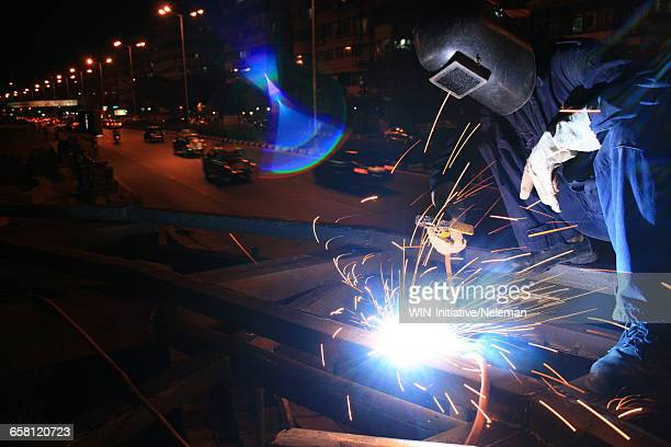 A worker welding a bus stop, India