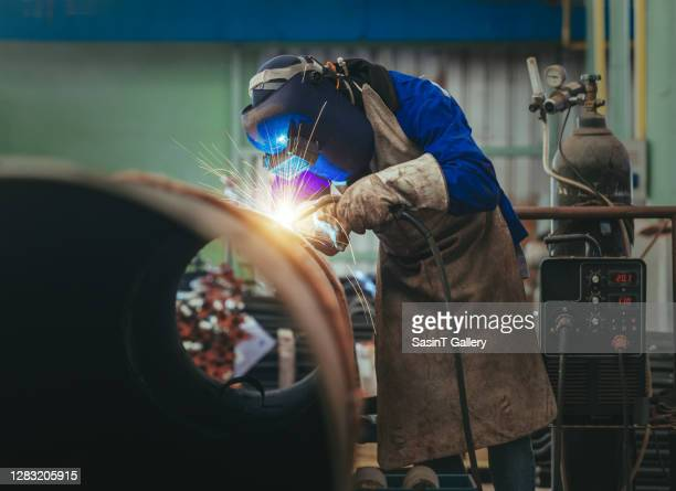 worker welding metal piping using mig welder - fabricage apparatuur stock pictures, royalty-free photos & images