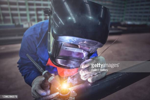worker welding metal piping using tig welder - fabricage apparatuur stock pictures, royalty-free photos & images