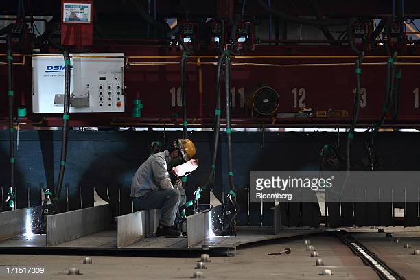 A worker welds a component of a ship under construction at the Daewoo Shipbuilding Marine Engineering Co shipyard in Geoje South Korea on Monday June...