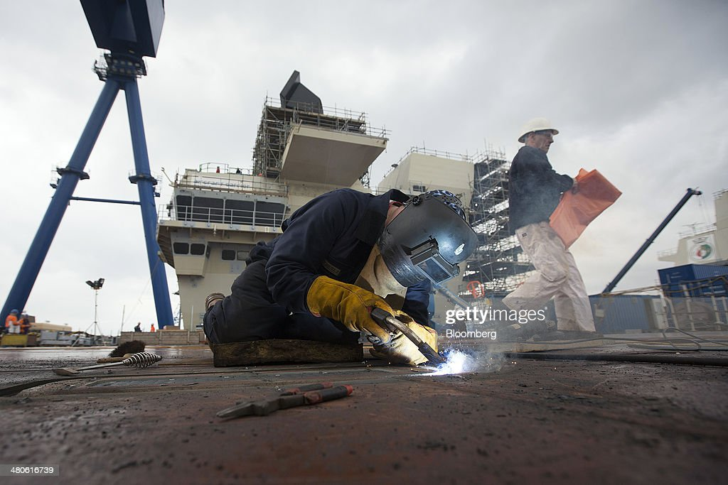 A worker welds a hatch door on the flight deck of the Royal Navy's new Queen Elizabeth class aircraft carrier, manufactured by the Aircraft Carrier Alliance, a joint operation between BAE Systems, Thales SA and Babcock International Group Plc, at Babcock shipyard in Rosyth, U.K., on Tuesday, March 25, 2014. Construction of hull sections for the HMS Queen Elizabeth and HMS Prince of Wales aircraft carriers is being undertaken at BAE's Scotstoun and Govan yards on the River Clyde in Glasgow, with the ships due to be assembled at Babcock International Group's dockyard in Rosyth, near Edinburgh. Photographer: Simon Dawson/Bloomberg via Getty Images