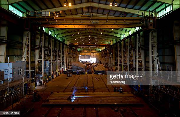 A worker welds a portion of a barge under construction at the Seaspan Vancouver Shipyard in North Vancouver British Columbia Canada on Wednesday Oct...