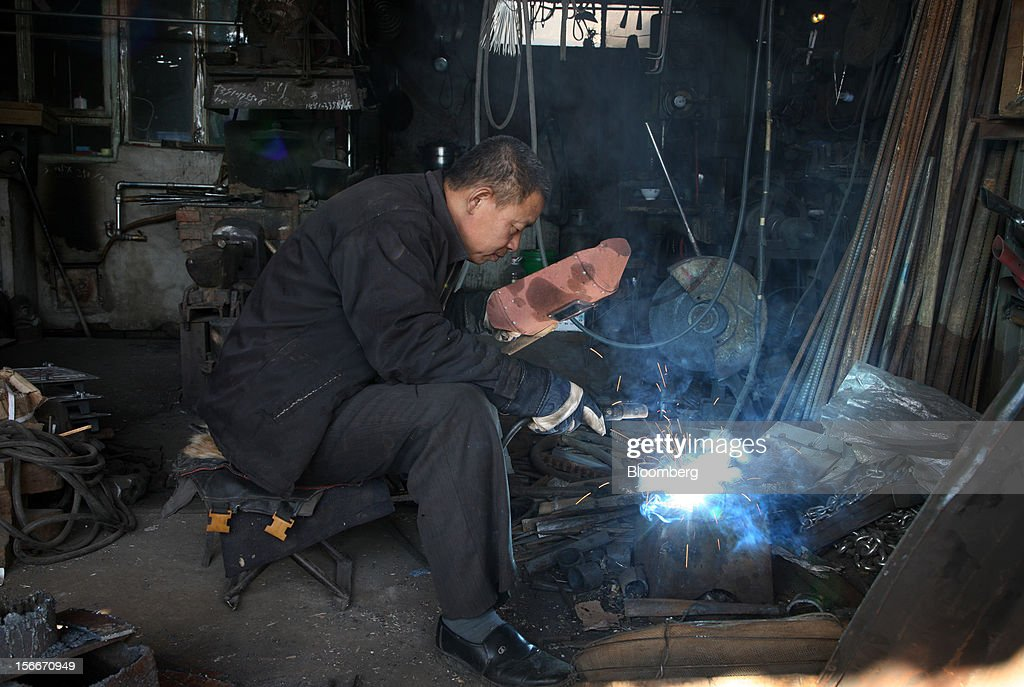 A worker welds a steel pipe at a workshop in Pinggu, on the outskirts of Beijing, China, on Saturday, Nov. 17, 2012. China's gross domestic product slowed to 7.4 percent in the July-September period from a year earlier, the weakest in three years. Photographer: Tomohiro Ohsumi/Bloomberg via Getty Images