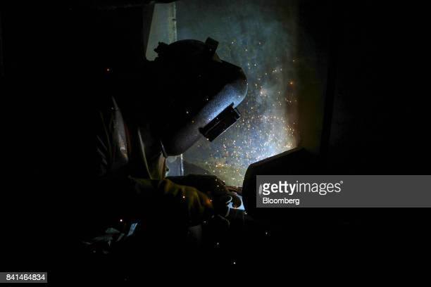 A worker welds at the Mumbai Metro Rail Corp casting yard in Mumbai India on Monday Aug 28 2017 The expanding mega city's suburban railway is one of...