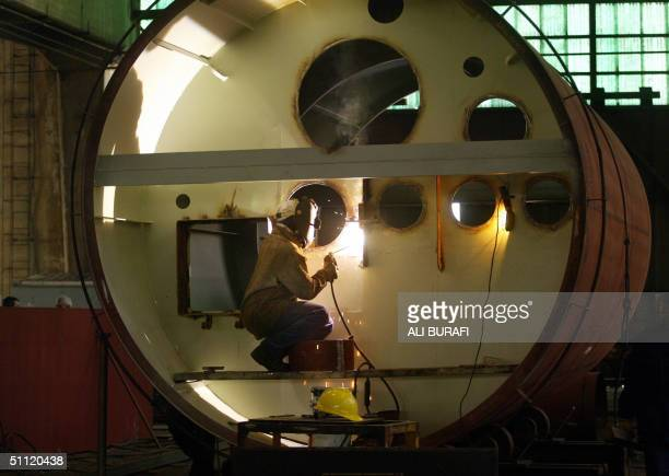 A worker welds inside a ship's funnel at the Rio Santiago shipyard in Ensenada La Plata 50 km from Buenos Aires on 26 July 2004 The Rio Santiago...