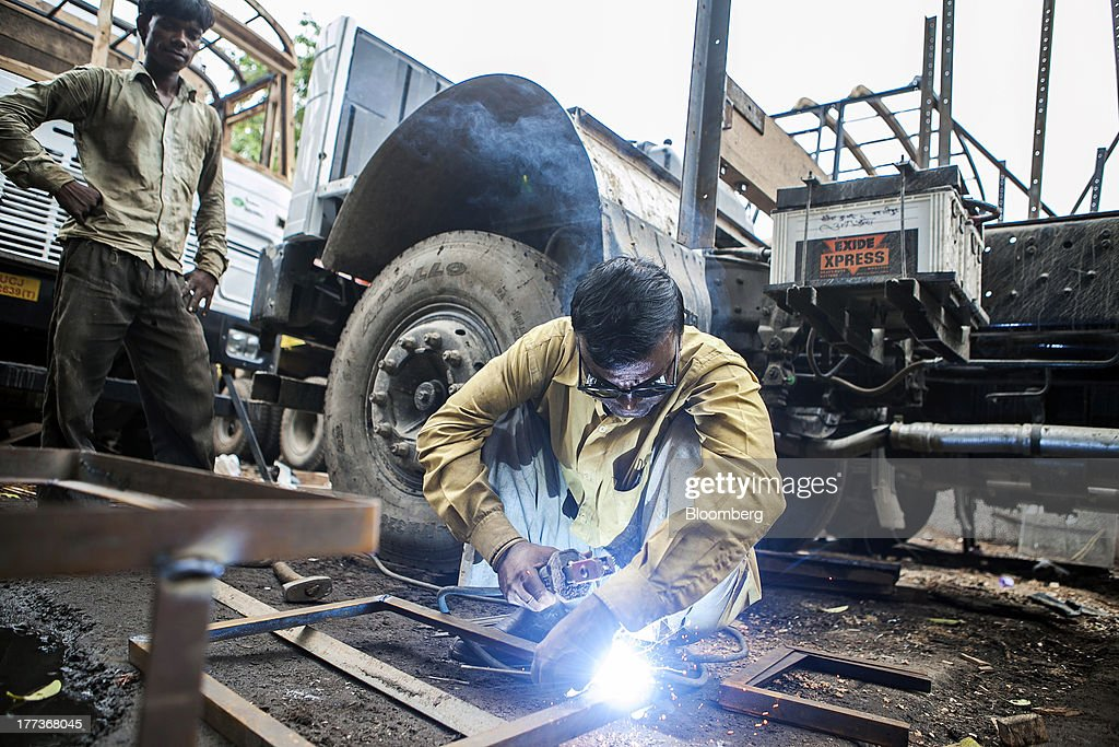 A worker welds pieces of metal during the restoration of a truck at the Sanjay Gandhi Transport Naga depot in New Delhi, India, on Thursday, Aug. 22, 2013. Indias rupee plunged 4.4 percent to a record this week in its worst performance since 1993 on signs the U.S. is getting closer to reducing stimulus that fueled demand for emerging-market assets. Photographer: Prashanth Vishwanathan/Bloomberg via Getty Images