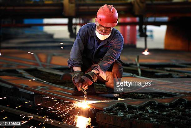 Worker welds steel in a factory in Huaibei, in north China's Anhui province on July 24, 2013. China's manufacturing activity contracted to a 11-month...