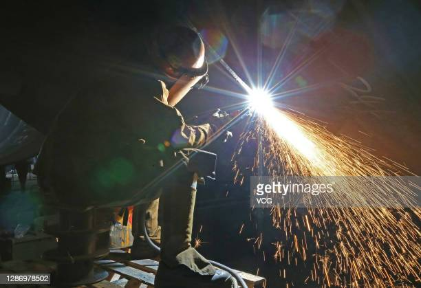 Worker welds steel pipe pile for offshore wind farm at a marine equipment manufacture company on November 21, 2020 in Yancheng, Jiangsu Province of...