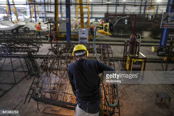 A worker welds the steel reinforcing frame of a precast concrete tunnel segment at the Mumbai Metro Rail Corp casting yard in Mumbai India on Monday...