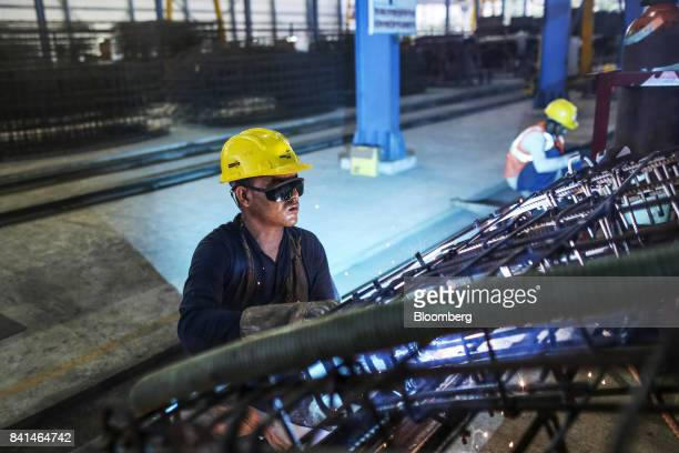 A worker welds the steel reinforcing of precast concrete tunnel segments at the Mumbai Metro Rail Corp casting yard in Mumbai India on Monday Aug 28...