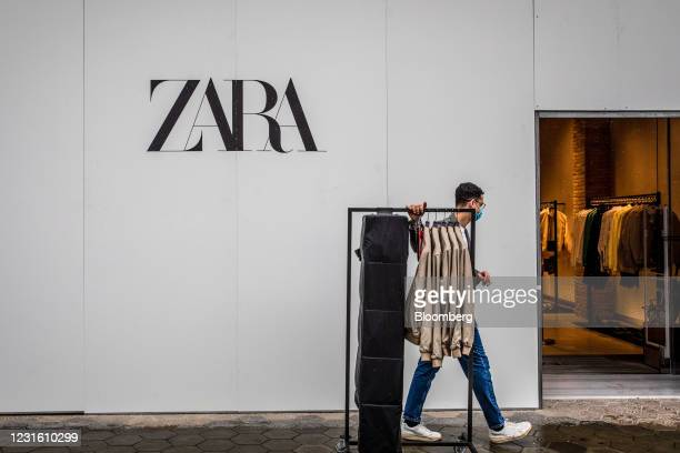 Worker wheels a clothing hangar into a Zara clothing store, operated by Inditex SA, in Barcelona, Spain, on Monday, March 8, 2021. Inditex will...