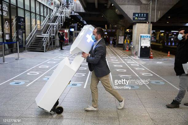 A worker wheels a hand gel dispensing unit near social distancing markers at Gare Montparnasse railway station in Paris France on Tuesday May 12 2020...