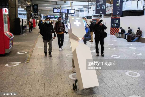 A worker wheels a hand gel dispensing unit over social distancing markers at Gare Montparnasse railway station in Paris France on Tuesday May 12 2020...