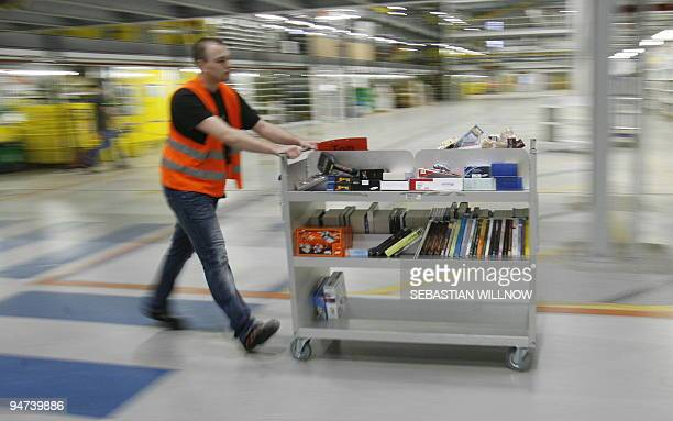 A worker wheels a trolley at the online retailer Amazon's distribution centre in the eastern German city of Leipzig on December 11 2009 AFP PHOTO DDP...