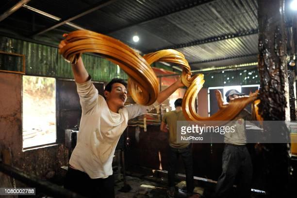 A Worker whipping semi Hard molasses to molasses Chaku at Tokha Kathmandu Nepal on Thursday January 10 2019 Molasses Chaku is usually prepared and...