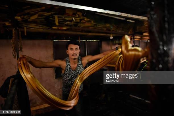 A Worker whipping semi Hard molasses to molasses Chaku at Tokha Kathmandu Nepal on January 10 2020 Molasses Chaku is usually prepared and consumed...