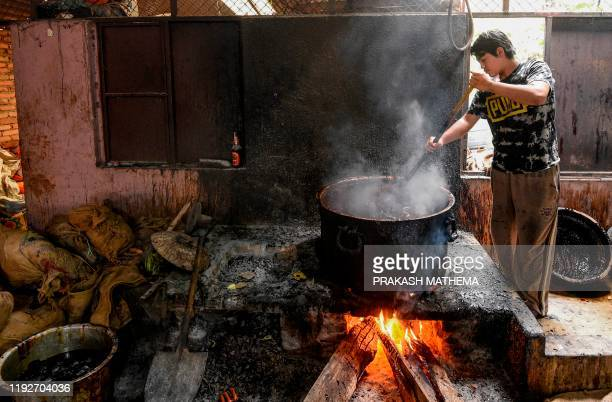 A worker whips molten raw hardened molasses locally know as Chaku for the upcoming Maghe Sankranti festival in Tokha on the outskirts of Kathmandu on...