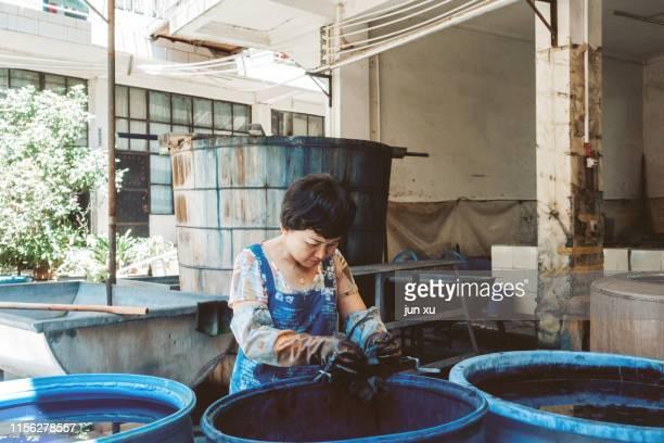 a worker who renders cloth in a blue dye vat - färbemittel stock-fotos und bilder