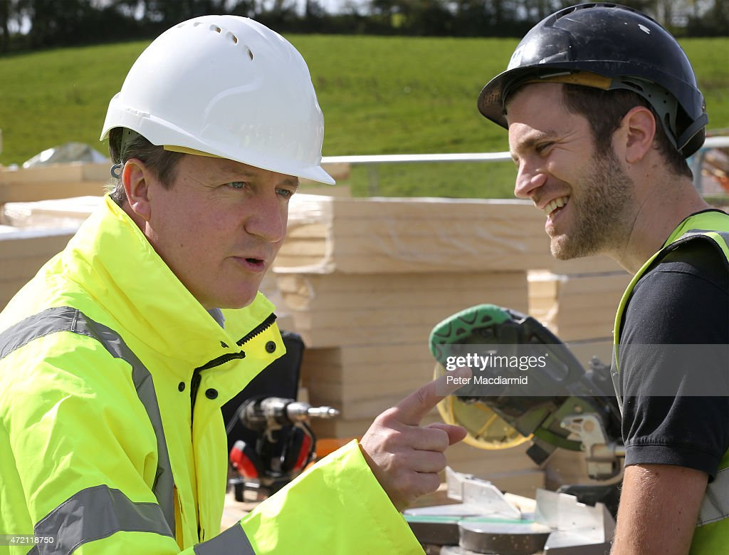 Worker Will Johnson looks on as Prime Minister David Cameron (L) gestures during a visit to a road construction site on May 4, 2015 near Bexhill, England. Campaigning is intensifying as the election enters it's last few days before voting begins on May 7, 2015.