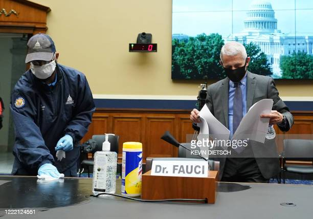 Worker wipes down the desk where Director of the National Institute for Allergy and Infectious Diseases Dr. Anthony Fauci will testify during the US...