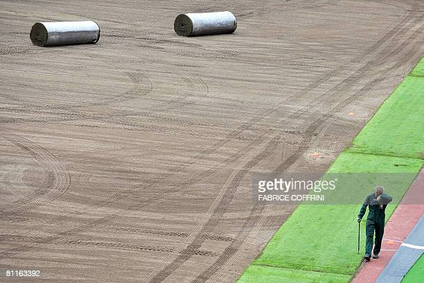 A worker wipes his forehead during the unrolling of a new natural lawn at the Letzigrund Stadium on May 20 2008 in Zurich Euro 2008 SA is now...