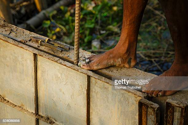 A worker with a bandaged toe works barefoot on a site on April 11 2016 in Khulna Bangladesh
