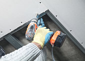 Worker with a drill screwdriver twists the screw into the drywall.
