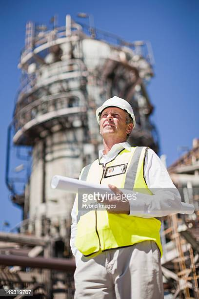 Worker with blueprints at oil refinery