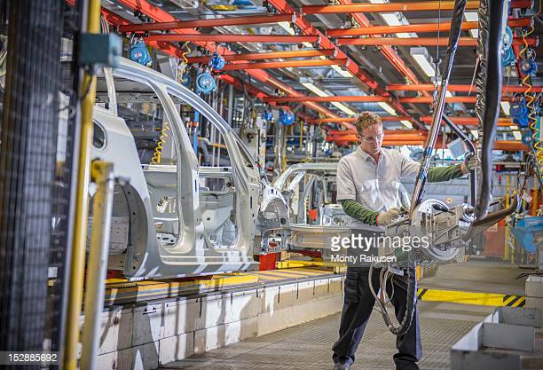 Worker with car bodies and machinery on production line in car factory