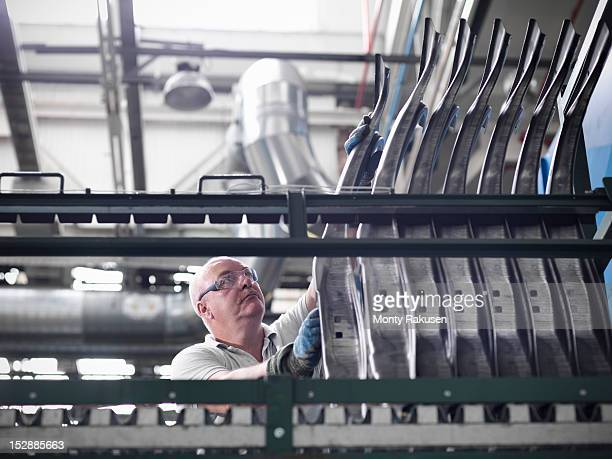 Worker with car parts in car factory
