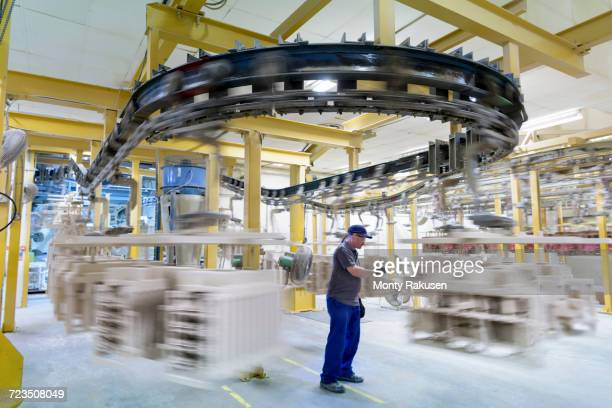 Worker with ceramic shelled wax components in drying area of precision casting factory