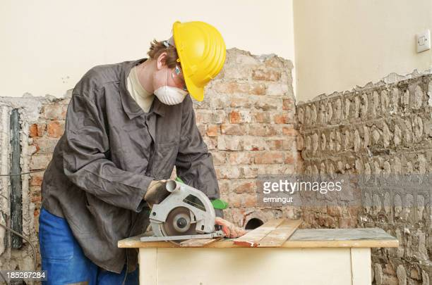 Worker with circular saw cutting