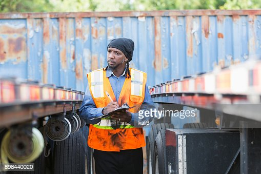 Worker with clipboard, standing between two semi-trucks