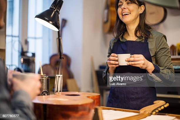 Worker with  coffee cup at guitar workshop