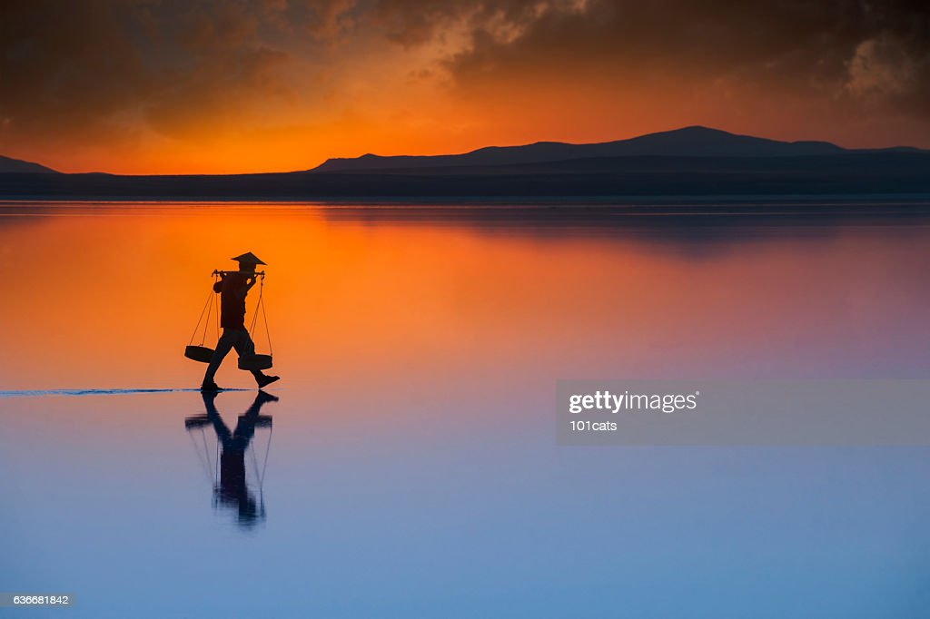 worker with conical straw hat, carrying salt on the water : Stock Photo