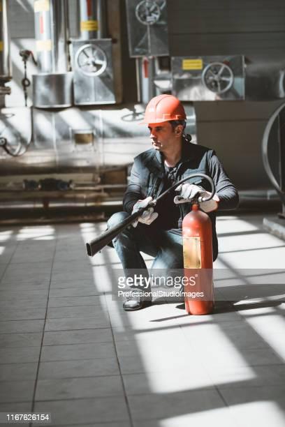 trabalhador com extintor de incêndio na estação de calor - extintor de incêndio - fotografias e filmes do acervo