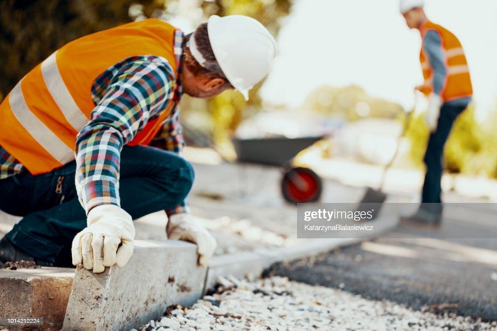 Arbeiter mit Handschuhen und Helm, die Vermittlung von Bordsteinen auf der Straße : Stock-Foto
