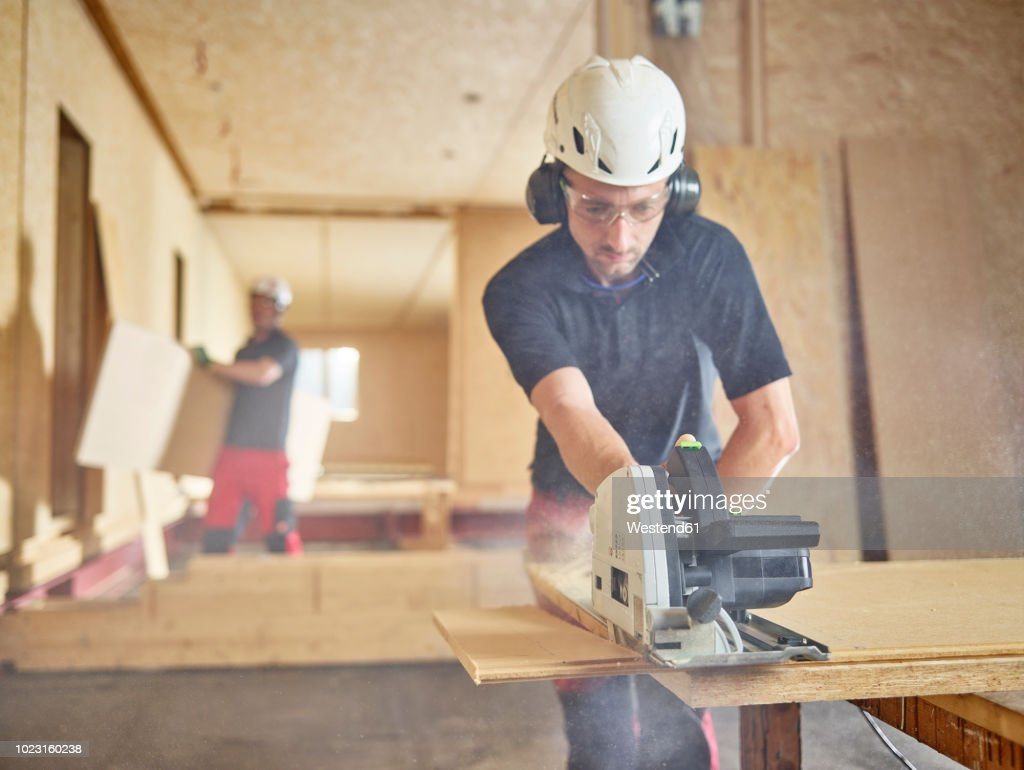 Worker with helmet sawing wood with circular saw : Stock Photo