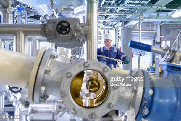 worker with process machinery in oil blending factory - ölindustrie stock-fotos und bilder