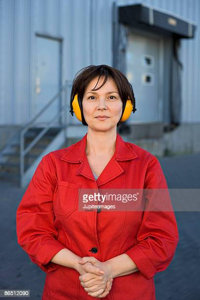 worker with protective headphones in front of warehouse - hearing protection stock pictures, royalty-free photos & images