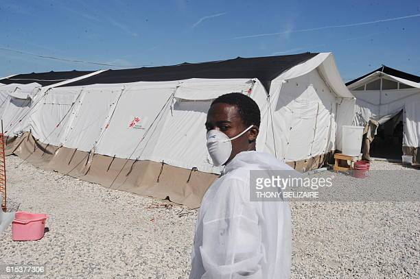 A worker with protective mask and clothing stands outside the hospital of MSF where cholera victims are being treated on December 22 2010 in Sarthe a...