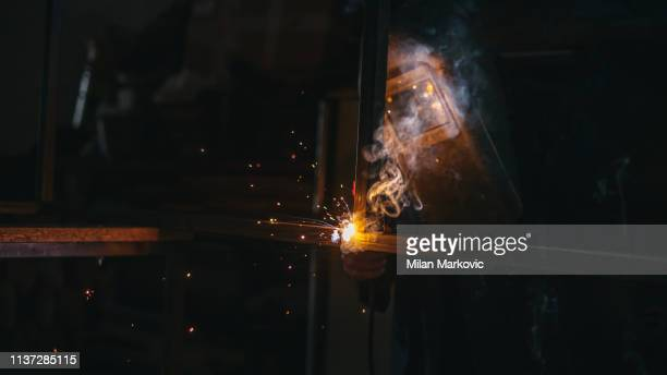 worker with protective mask welding metal - in flames i the mask stock pictures, royalty-free photos & images