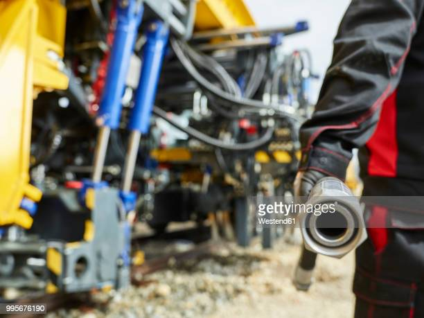 Worker with reserve hose line in front of machine