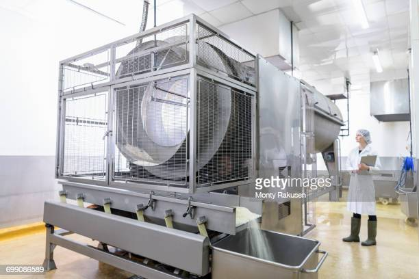 Worker with rice cooking machine in Asian food factory