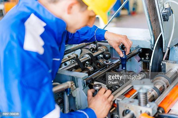 Worker with screwdriver fixing the machine